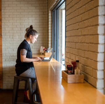 Woman working on laptop while eating at Maple Street Biscuit's Jacksonville Beach store