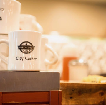 photo of Maple Street coffee mugs lined up inside the City Center location