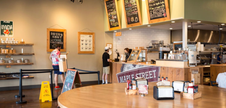 photo of round community table looking towards the front counter at the Gainesville Maple Street location
