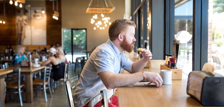 Man sitting at counter, eating, facing front window at Maple Street Biscuit's Killearn store