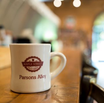 coffee mug with Maple Street logo and Parsons Alley on it sitting on a wooden counter