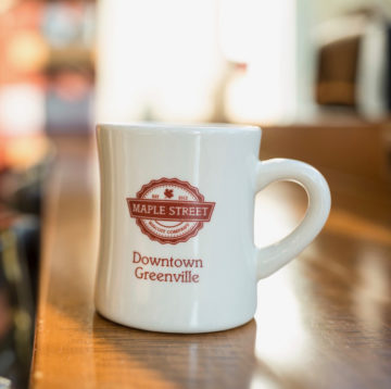 Maple Street Biscuit coffee mug on counter in Downtown Greenville location