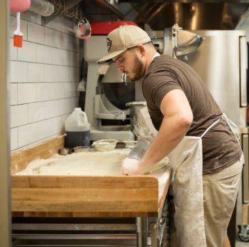 Employee rolling out biscuit dough on wooden counter at Maple Street Biscuit Company's Tioga store